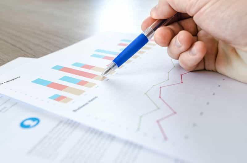 Sebuah tangan yang memegang pena menunjuk ke grafik keuangan di atas kertas.