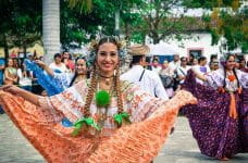 A woman dancer wearing traditional costume smiles at the camera during a performance in Costa Rica.