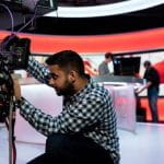 Seorang juru kamera mengatur tripod di stasiun TV.