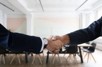 A handshake confirming a deal or acquisition occurring in a meeting room in a corporate office.