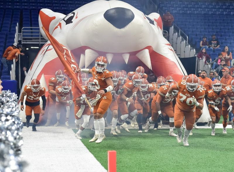 Sebuah tim sepak bola Amerika berseragam oranye berlari ke lapangan.