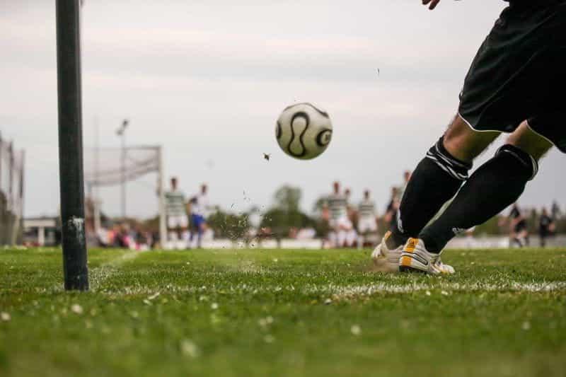 Seorang pemain sepak bola menendang bola dengan pemain di lapangan.
