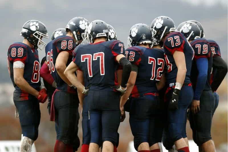 Sebuah tim sepak bola Amerika berkumpul untuk mendiskusikan pertandingan berikutnya.