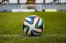 A football on a green grass pitch.