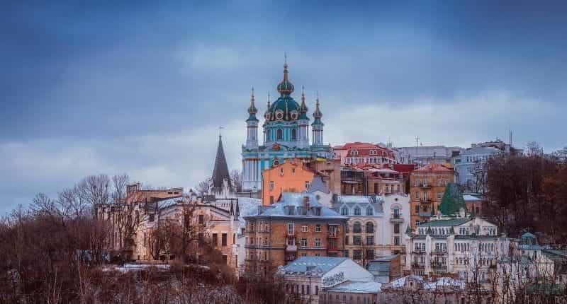 Gereja Kristen Ortodoks yang berdiri di atas bukit di ibu kota Ukraina, Kiev, dikelilingi oleh bangunan berwarna-warni.