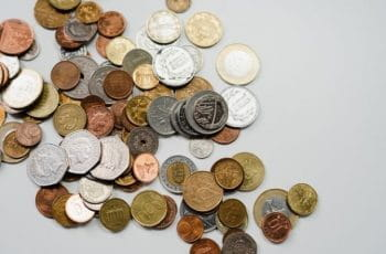 Coins from around the world scattered on a table.