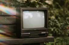 A retro TV on a park bench.