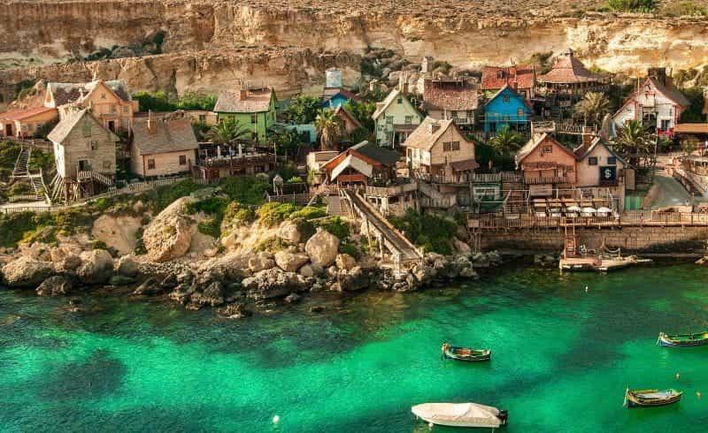 Sebuah desa nelayan pesisir pantai Malta, dihuni oleh gubuk-gubuk kecil dan rumah-rumah serta banyak perahu.