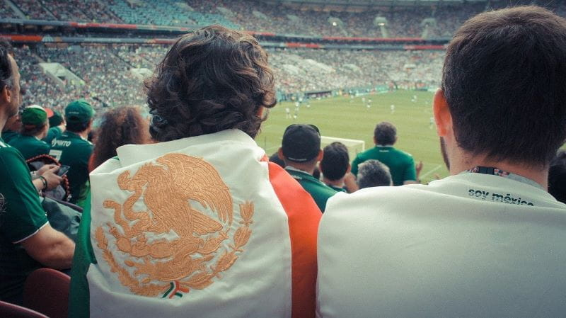Seorang penggemar sepak bola yang dibalut dengan bendera Meksiko menonton pertandingan langsung di stadion yang ramai.