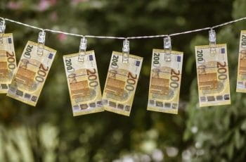 A series of €200 notes drying on a clothesline, held up by clothes pins.