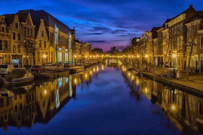 Pemandangan malam di kota Belanda, dengan kanal indah yang diapit oleh deretan rumah, mobil, dan perahu di kedua sisinya.
