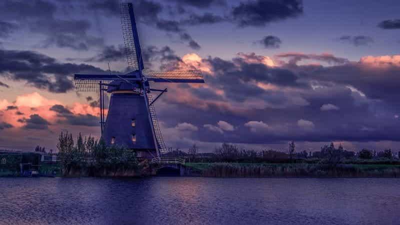 Kincir angin Belanda yang khas di tepi air, dengan lapangan terbentang di belakang dan ke samping.