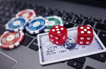 Several poker chips and a set of die resting atop a credit card and laptop.