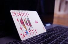 Five poker cards leaning against an open laptop screen.