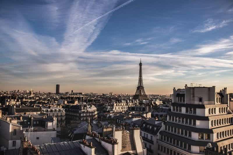 Cakrawala Paris di bawah langit biru, dengan Menara Eiffel yang terkenal dipajang secara mencolok.