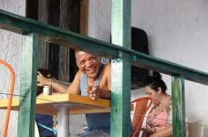 A man smiles at a table in a café in Puerto Rico.