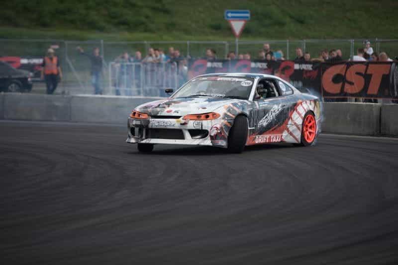 Sebuah mobil balap yang melayang di lintasan, mengeluarkan asap di depan penonton sebagai latar belakang.