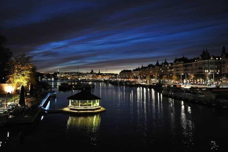 Ibu kota Swedia, Stockholm, saat matahari terbenam, dengan saluran sungai yang dikelilingi lampu dan dermaga di tengah.