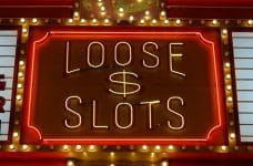 A lit-up neon casino sign, reading LOOSE $ SLOTS.