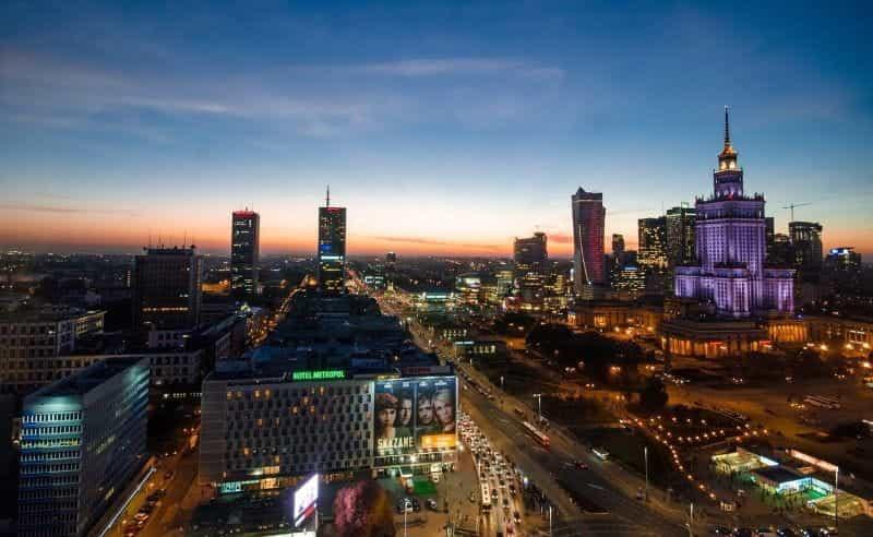Kaki langit malam hari Warsawa ibu kota Polandia, menampilkan gedung pencakar langit terkemuka dan jalan raya besar.