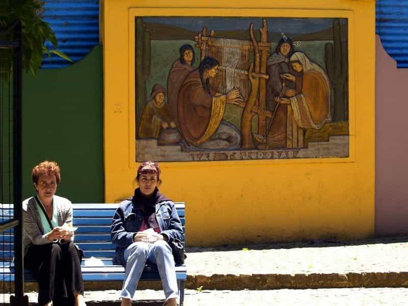 Dua wanita duduk di bangku di depan lukisan dinding di Buenos Aires, Argentina.
