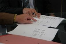 Two individuals looking over a bid or offer agreement, pointing to various figures and information in the document.