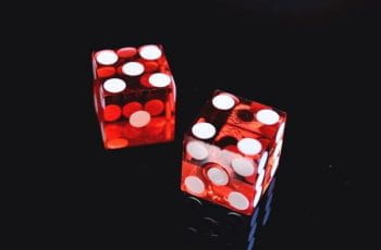 A pair of red dice on a black background.