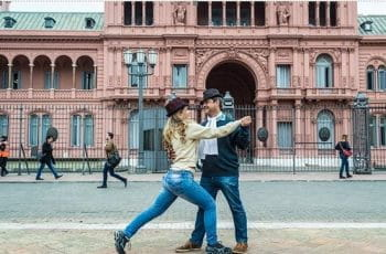 A man and woman tango in front of Argentina's Casa Rosada.