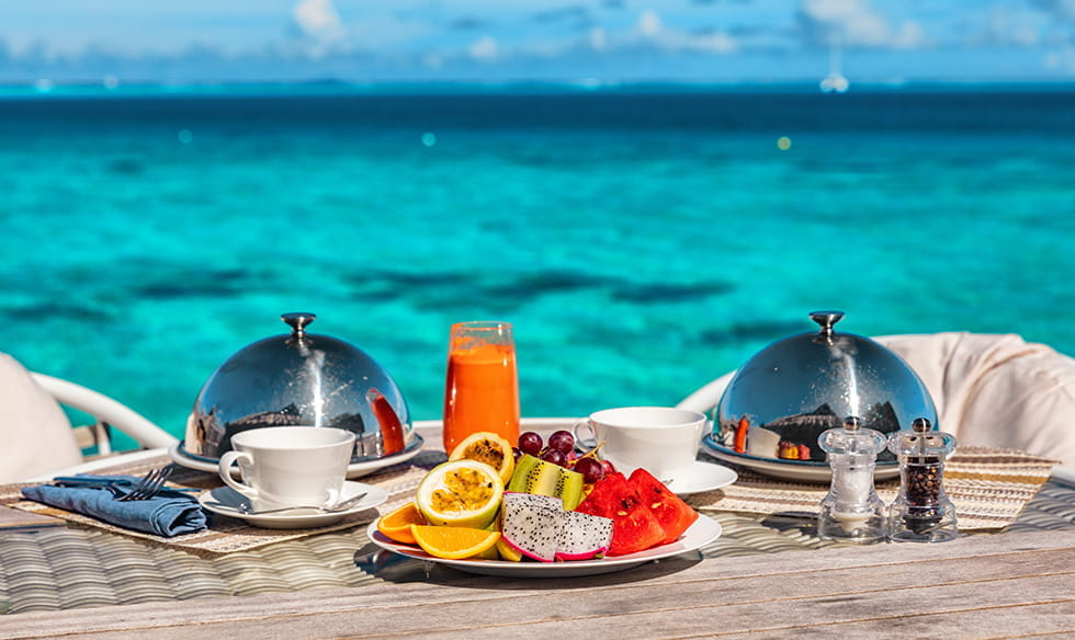 A fruit platter and crockery in front of the ocean.