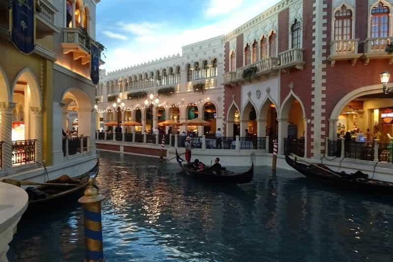 Seorang pendayung gondola mengarahkan gondola menyusuri kanal di Venesia.