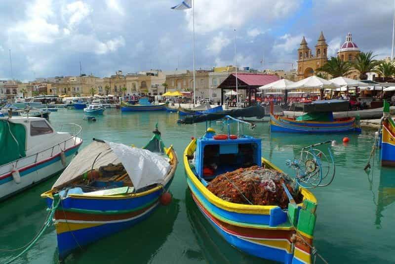 Desa nelayan tradisional Malta, Marsaxlokk, dengan pelabuhan berwarna-warni dan perahu yang dipamerkan.