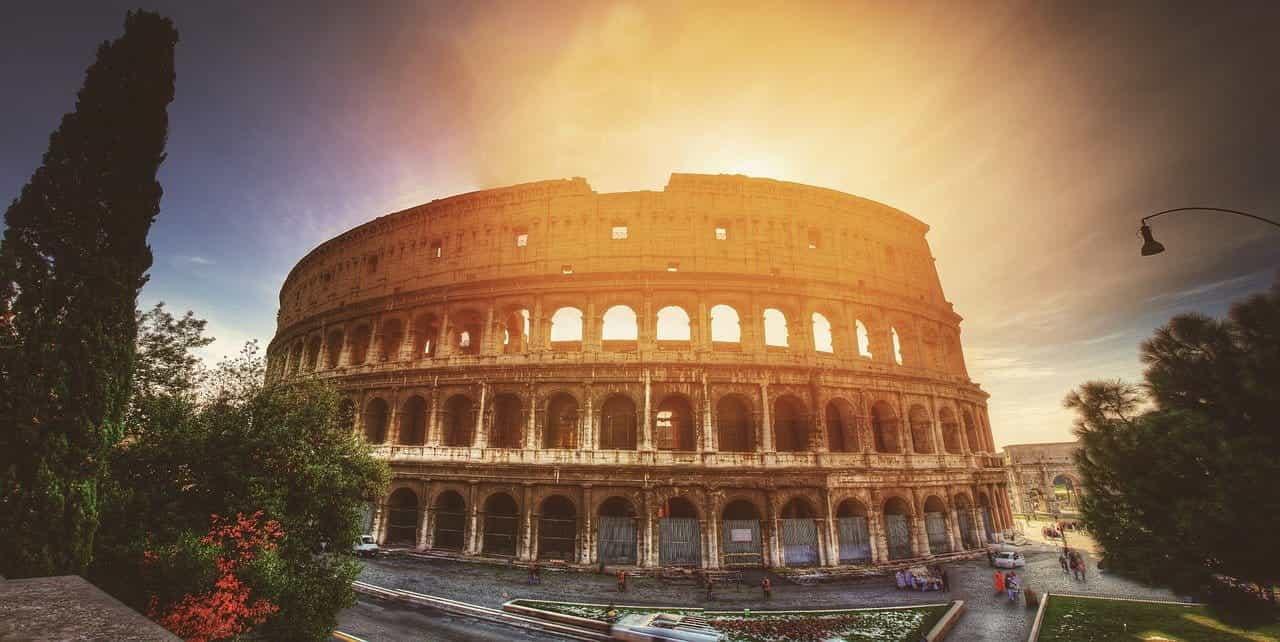 Colosseum yang terkenal di dunia di ibu kota Italia, Roma, dengan matahari bersinar tepat di belakangnya.