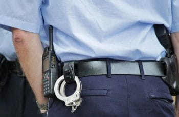 The backside of a police officer, equipped with a pair of handcuffs, a radio and a handgun.