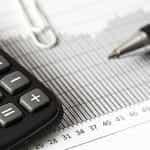 A calculator and a pen next to a financial graph.