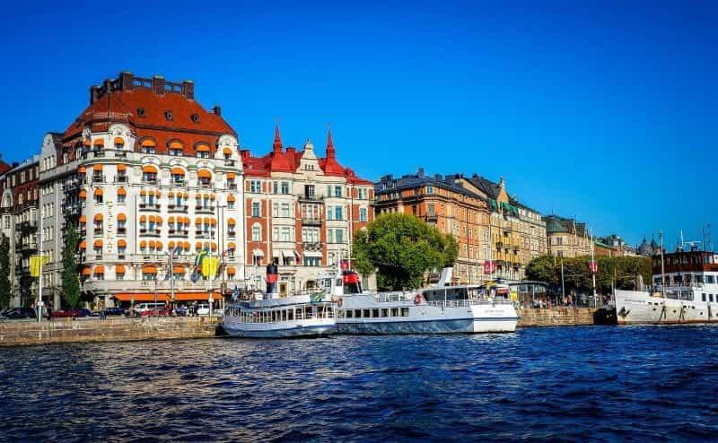 Teks Alt: Tepi pantai ibu kota Swedia, Stockholm, pada hari yang cerah dan cerah, dengan beberapa kapal feri di tengahnya.