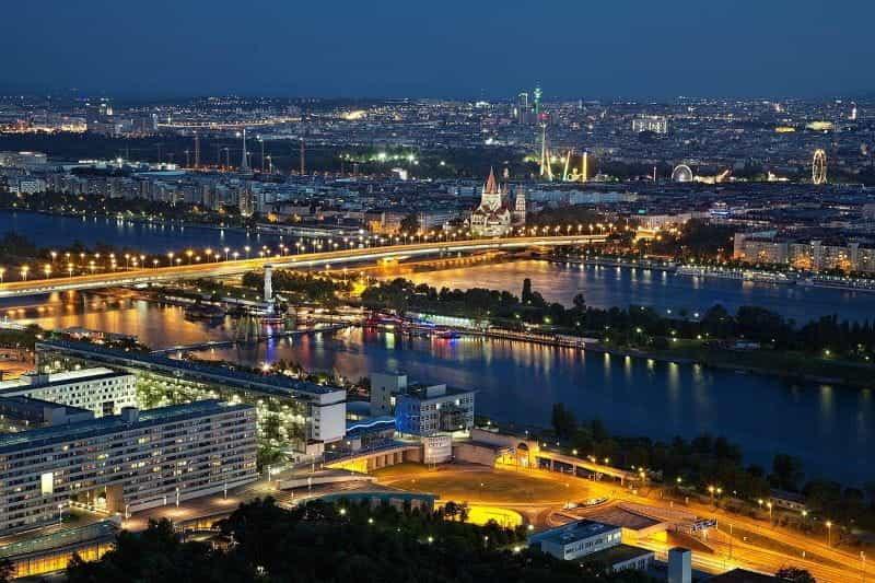 Ibu kota Austria, Wina, dengan jembatan besar dalam tampilan penuh bersama dengan banyak bangunan dan gereja yang menyala.
