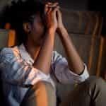 Seorang wanita stres duduk dengan punggung di sofa dengan wajah di tangannya.