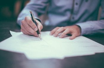 A man seated at a desk signing a piece of paperwork with a pen.