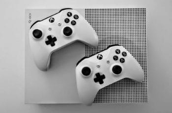 Microsoft's Xbox One gaming system, with two white and black controllers resting atop the console itself.