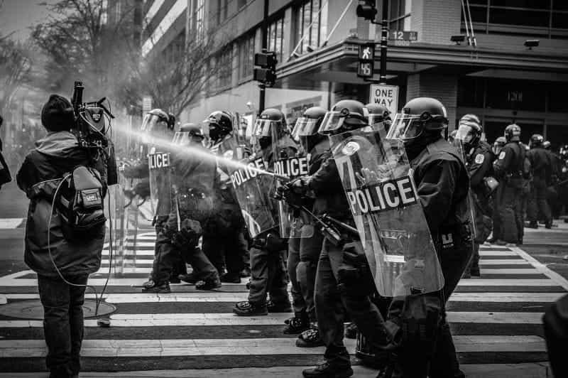 Polisi bersenjata membela diri dari kerusuhan.