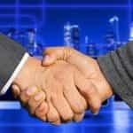 Jabat tangan antara dua orang dengan setelan jas gelap.