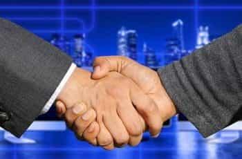 A handshake between two people in dark suits.
