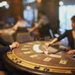 Dealer blackjack meletakkan kartunya di atas meja kartu.