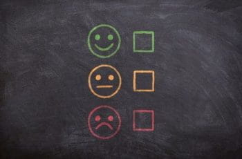 Three faces drawn on a chalkboard, ranging from smiling to satisfied to unhappy.