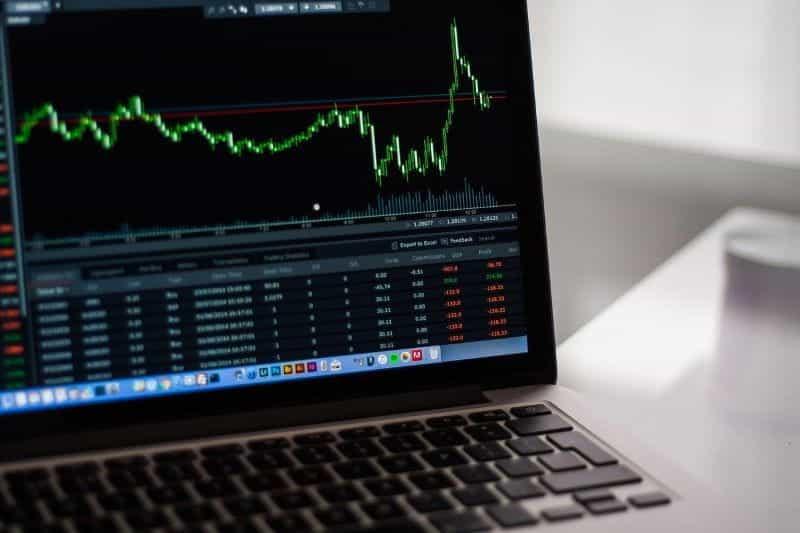 Sebuah laptop terbuka ke jendela grafik yang menggambarkan nilai saham naik dan turun.