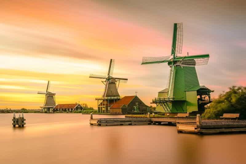 Tiga kincir angin klasik Belanda di tepi perairan saat matahari terbenam.