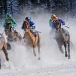 Enam joki berpacu dengan kudanya di atas salju.