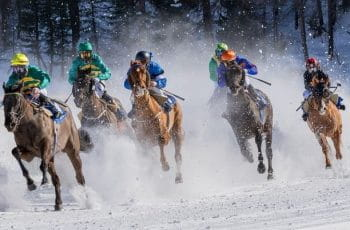 Six jockeys racing their horses in full gallop in the snow.