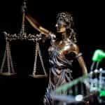 Patung keadilan buta yang menimbang timbangannya dengan kereta belanja di latar depan.