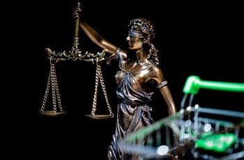 A statue of blind justice weighing its scales with a shopping cart in the foreground.